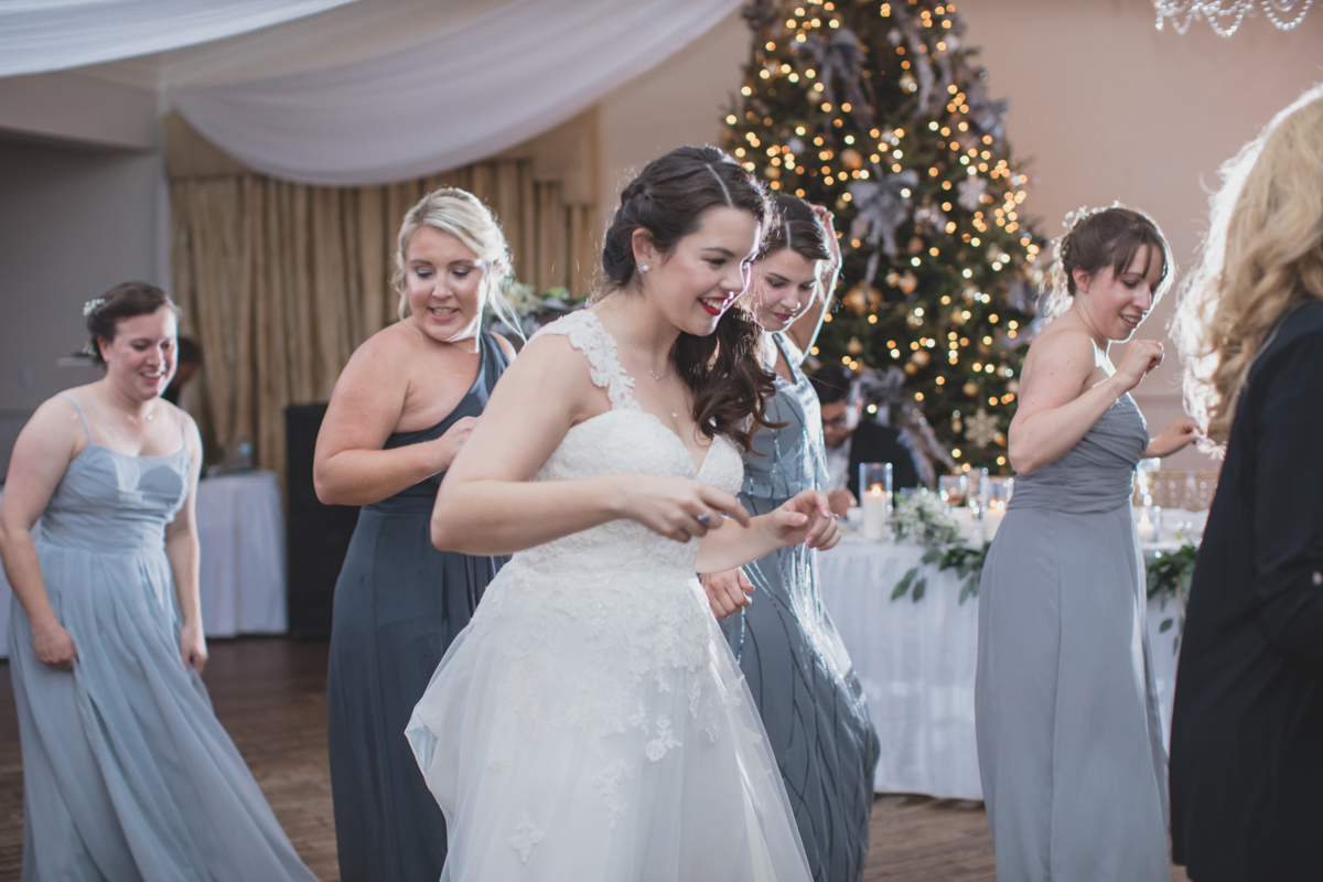 bride and bridesmaids on dancefloor doing a line dance for Highland Manor wedding