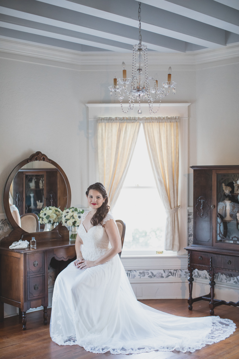 bride sitting at vintage vanity next to window
