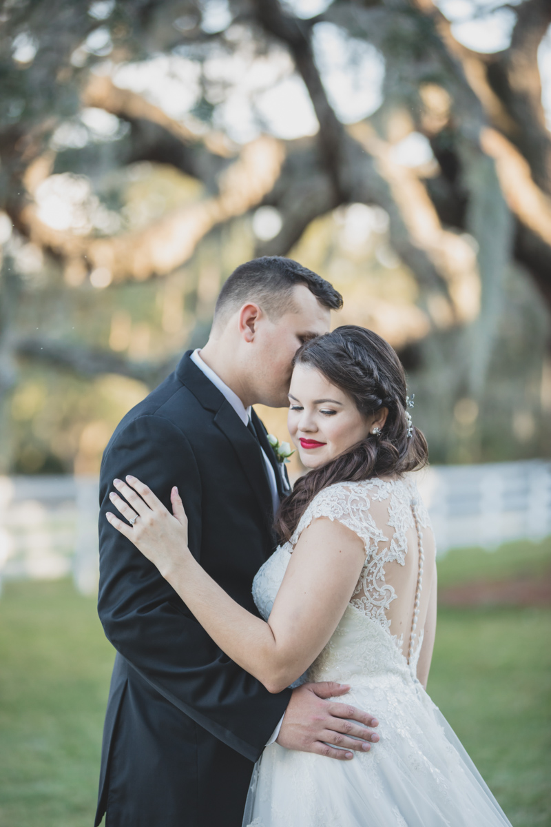 bride in red lipstick smiling and hugging groom