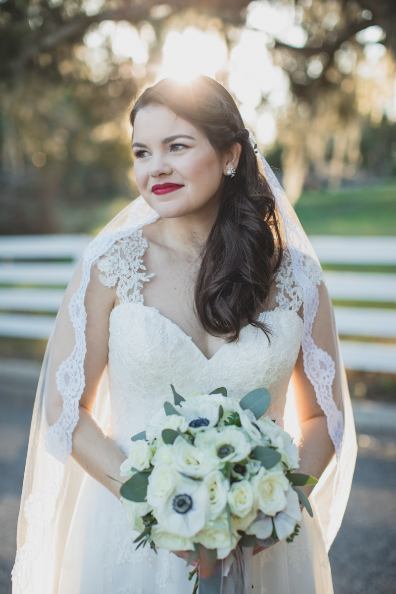 bride looking to the side holding white bouquet and in lace veil