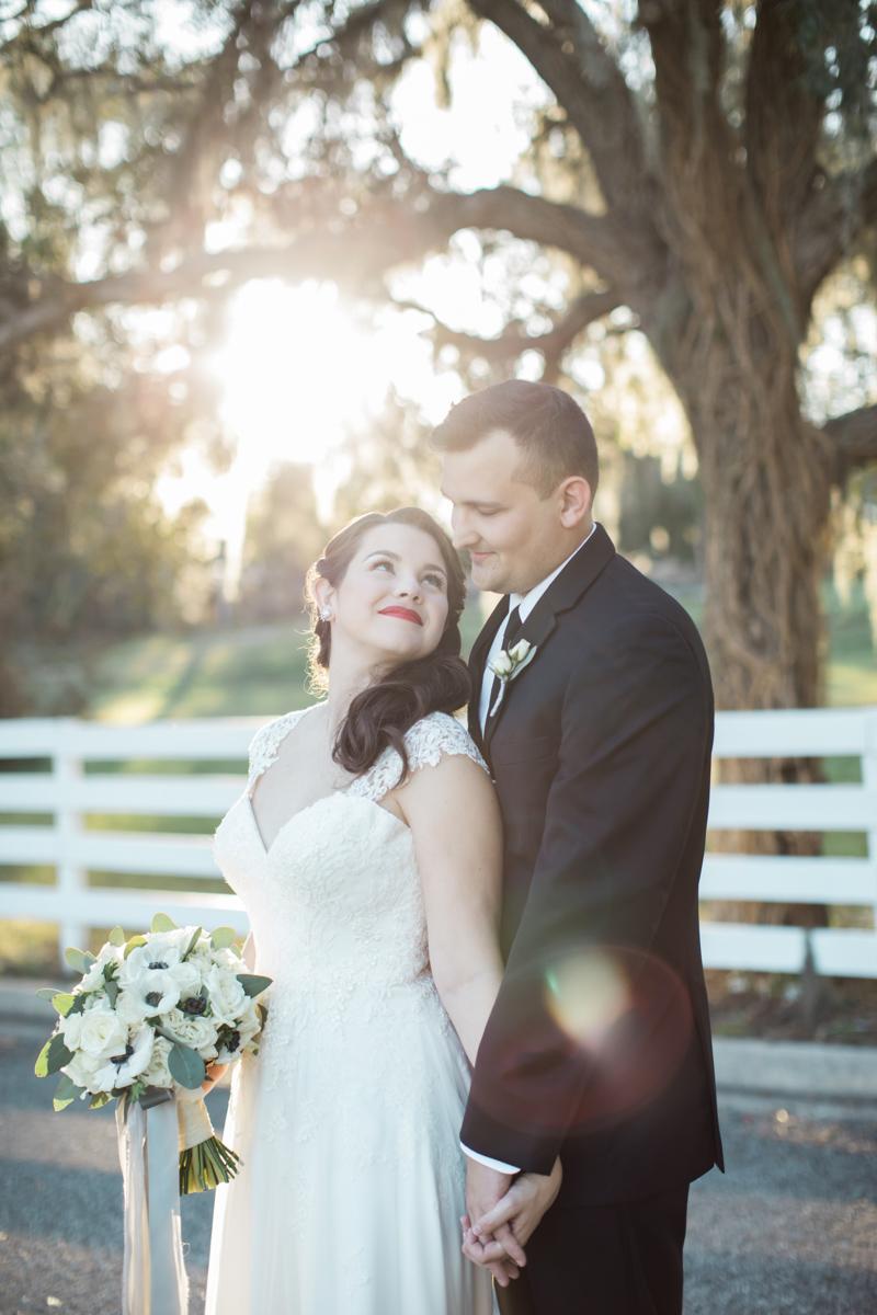 bride looking behind her at her groom in a black tux