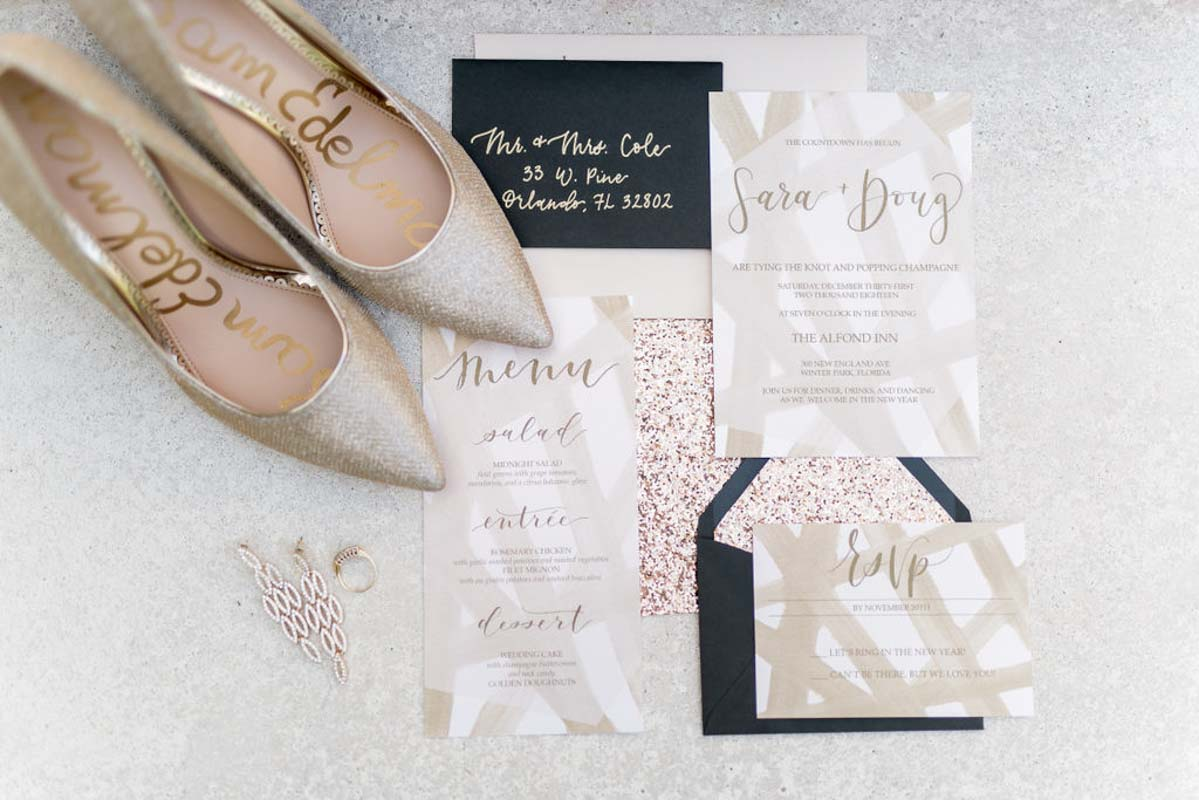 black and gold wedding invitations next to champagne bridal shoes