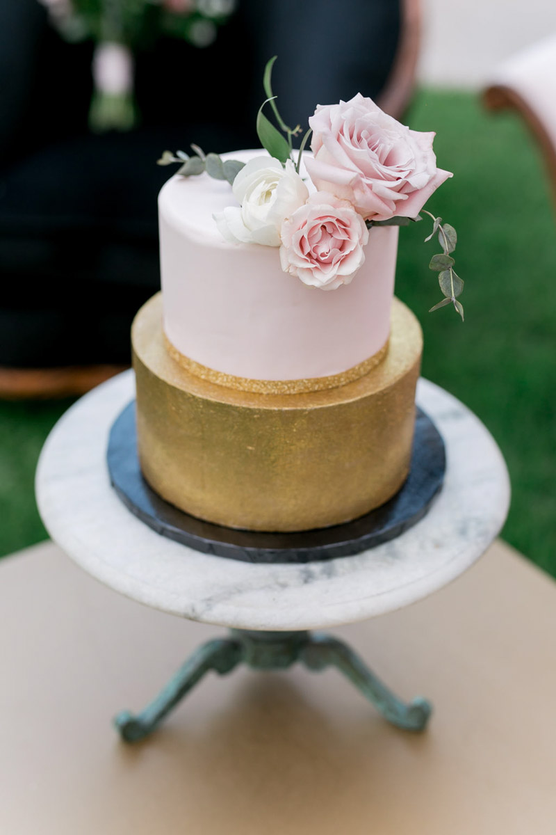 blush and gold wedding cake on top of marble cake stand