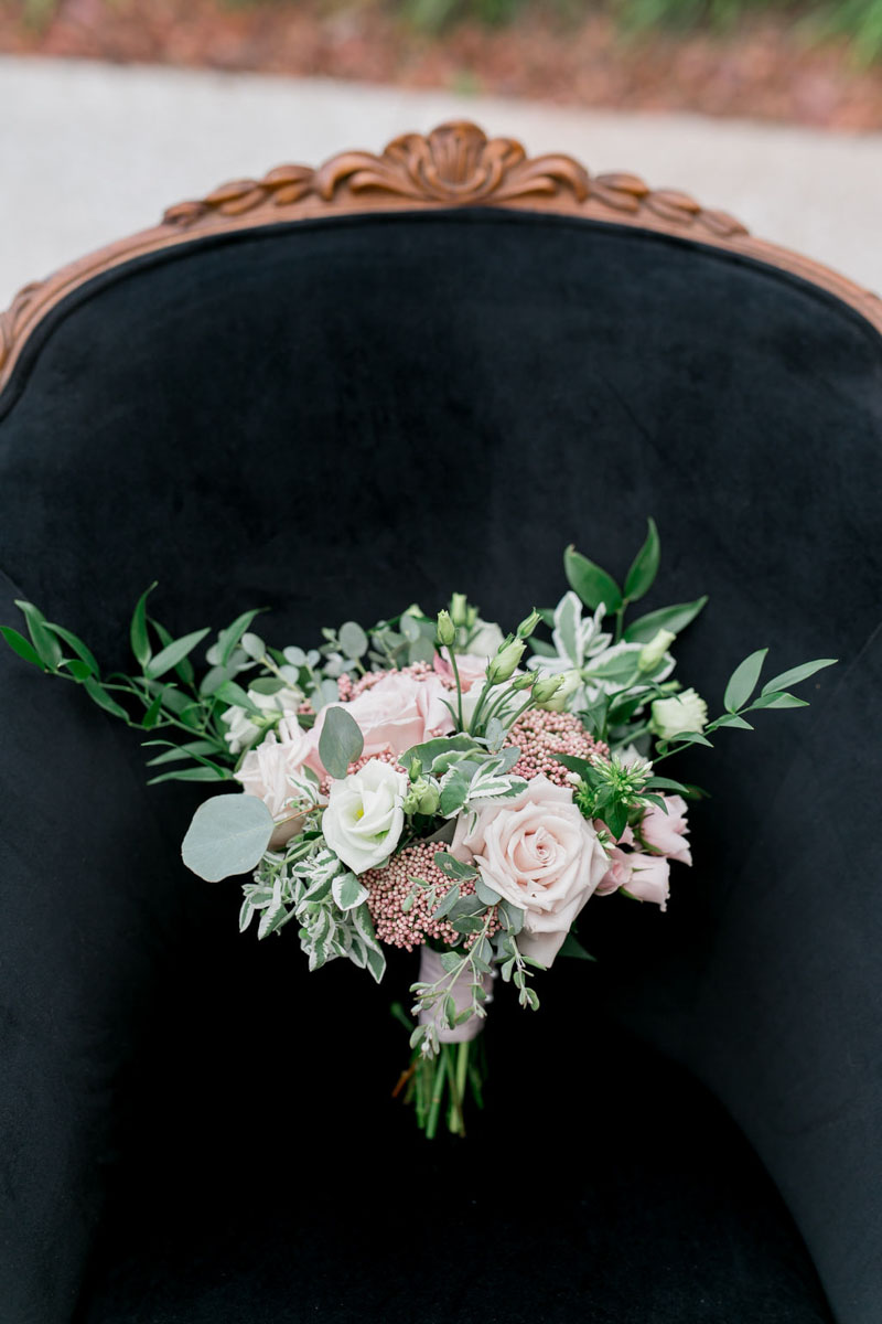 blush and white bridal bouquet on black antique chair