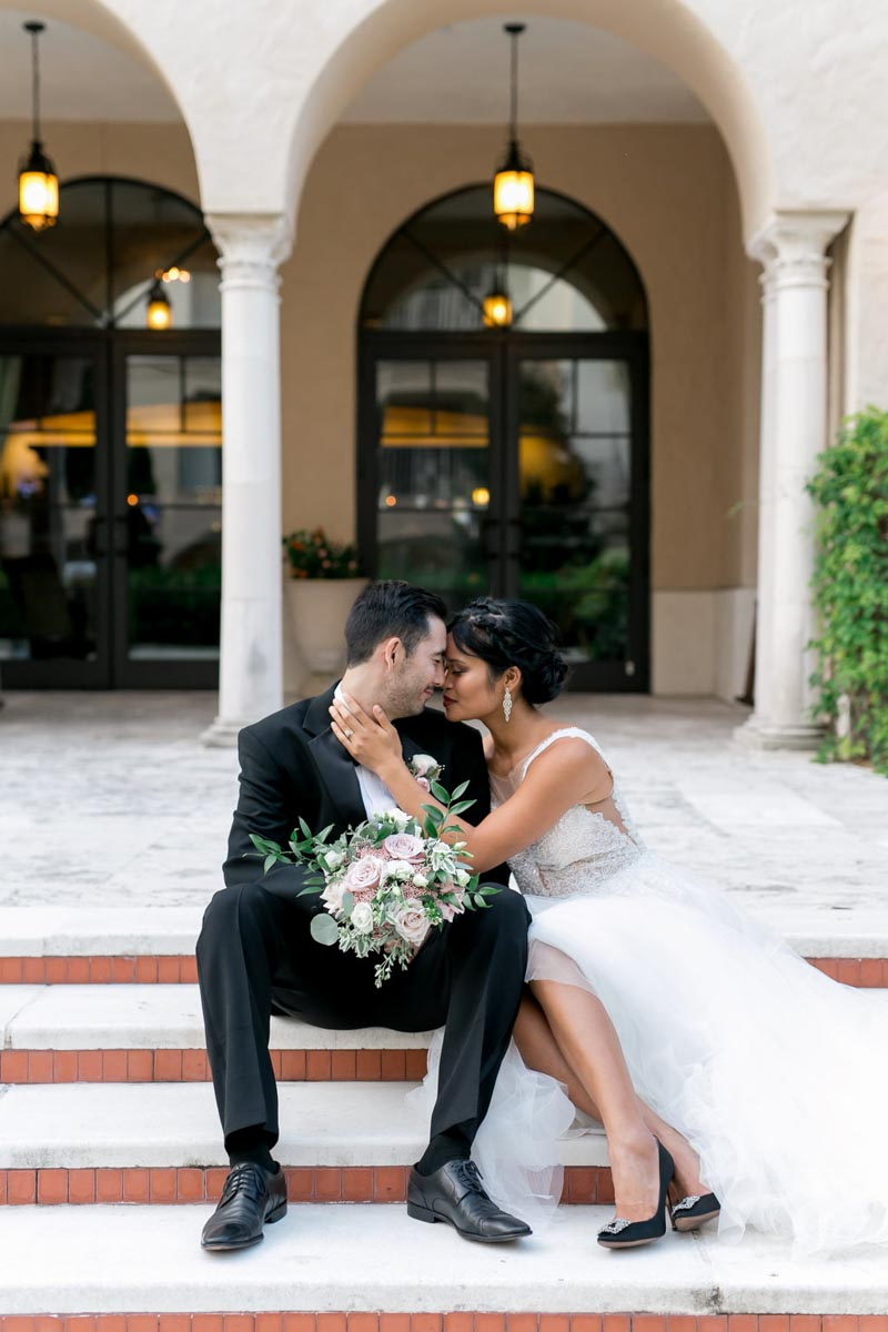 couple sitting on steps at the Alfond Inn for New Years Eve wedding shoot