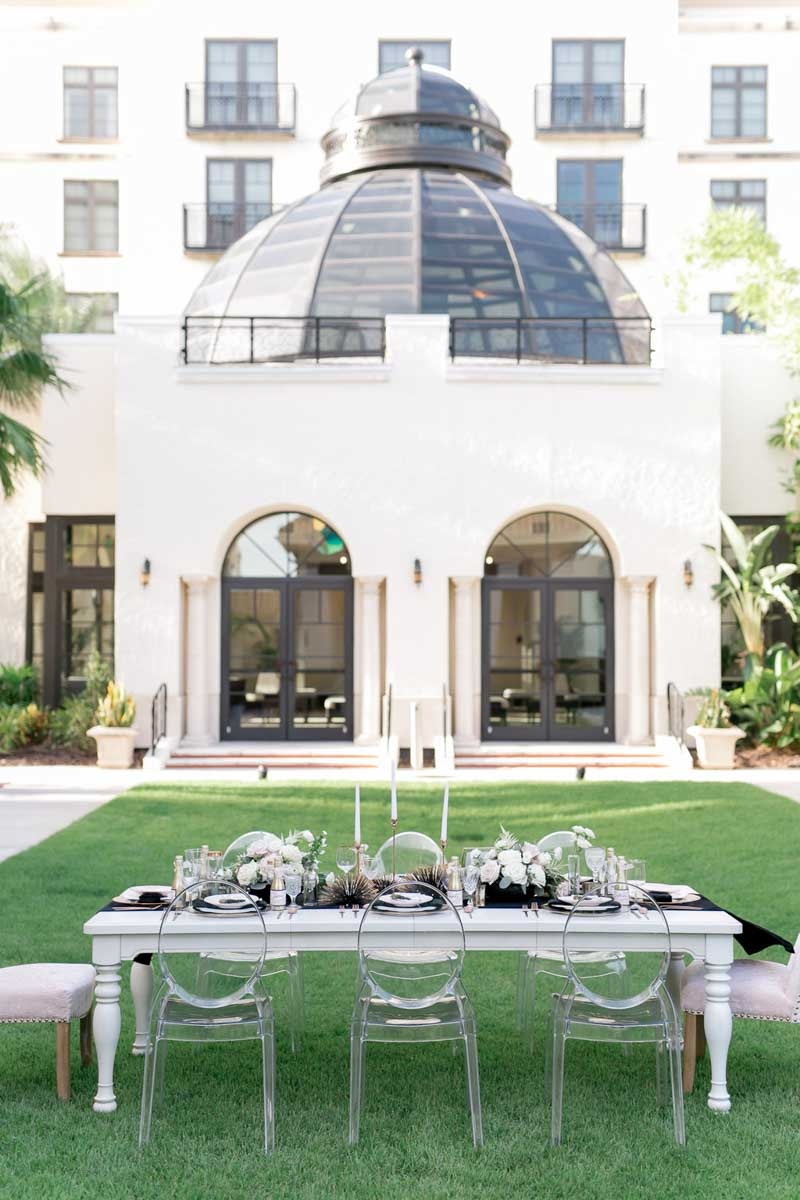 white reception table with ghost chairs in courtyard