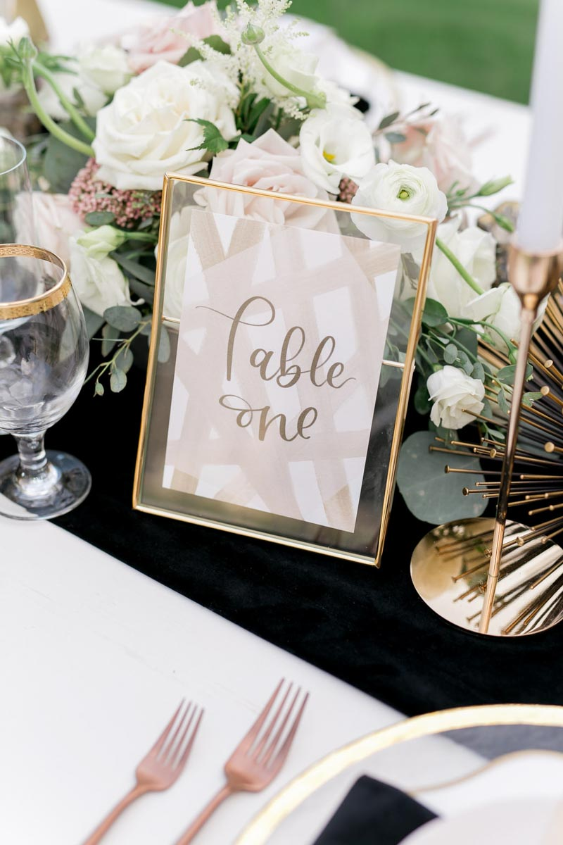 gold framed calligraphy table number on black runner