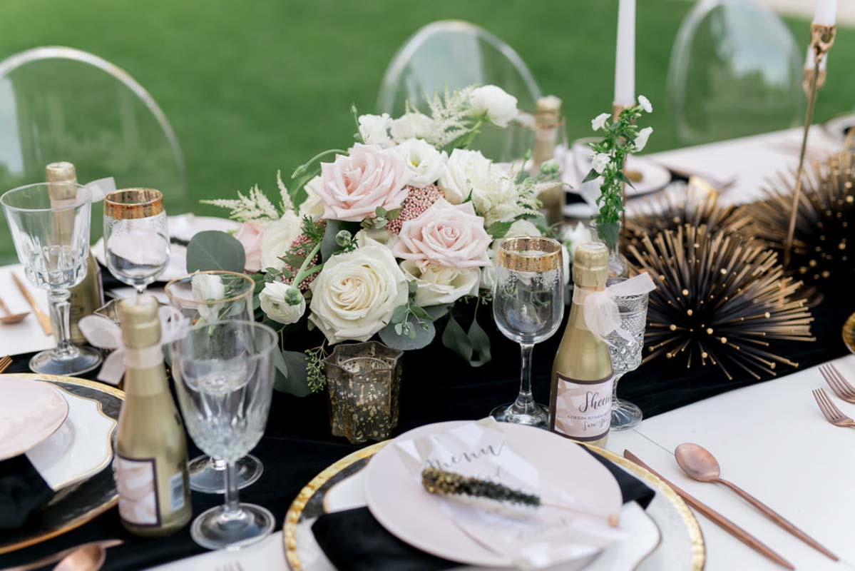 blush and white wedding centerpiece with gold accents on black table runner