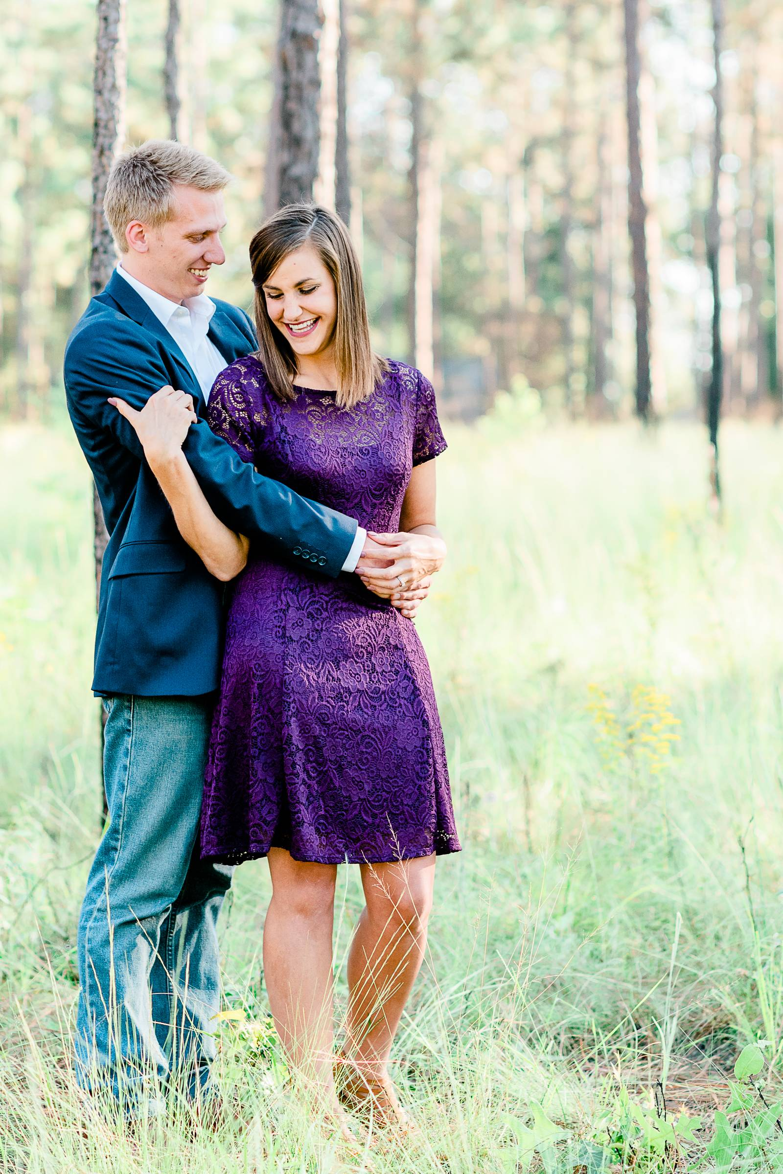 man hugging woman in purple dress for engagement session