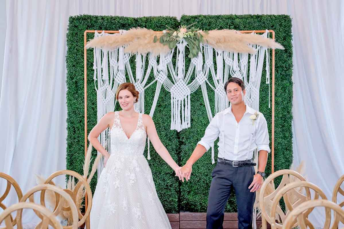 couple standing in front of macrame wedding ceremony arch holding hands