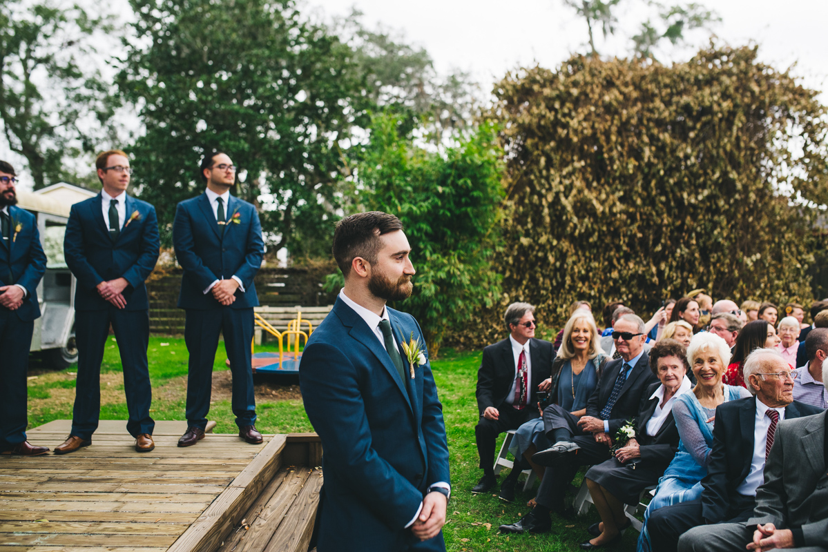 groom watching bride walk up aisle for outdoor wedding ceremony