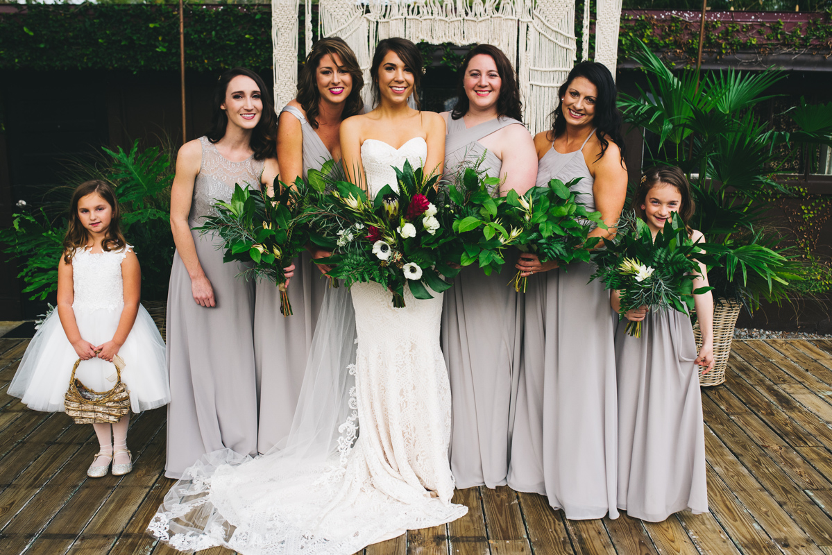 bridesmaids in light grey dresses hold organic style bouquet with bride