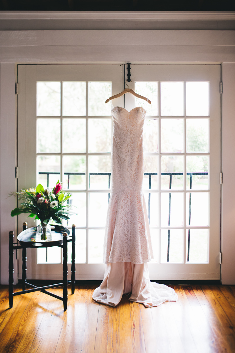 unique lace wedding gown hanging from french doors at The Acre Orlando