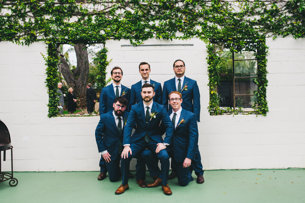 groom with groomsmen in front of white block wall with vines