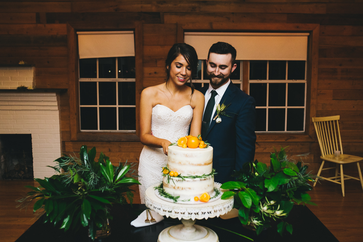 couple cutting their wedding cake with oranges on it.