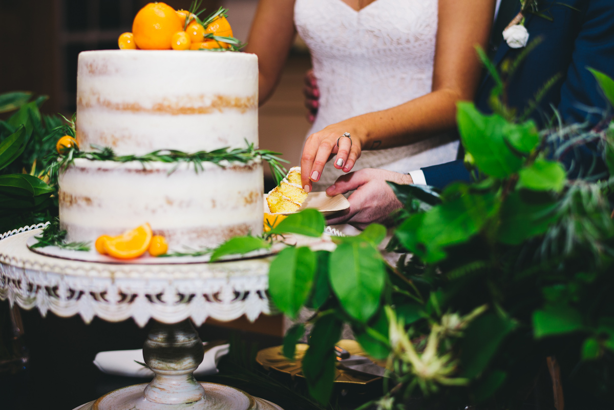 semi naked wedding cake with oranges on it