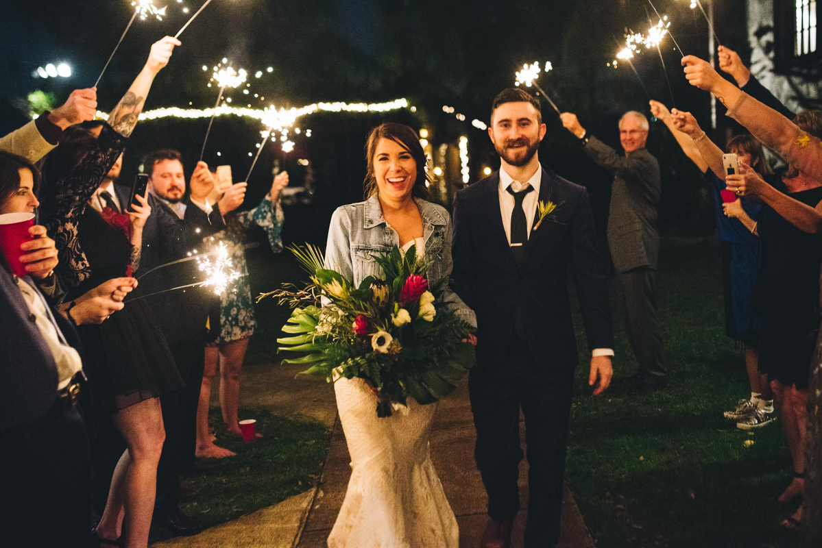 bride and groom walking through a sparkler exit smiling