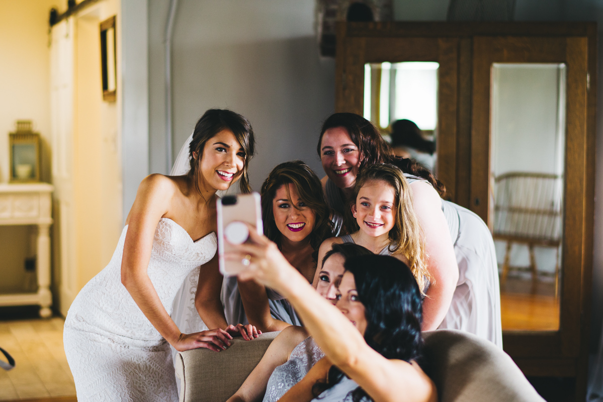 bride taking a selfie with her bridesmaids before wedding
