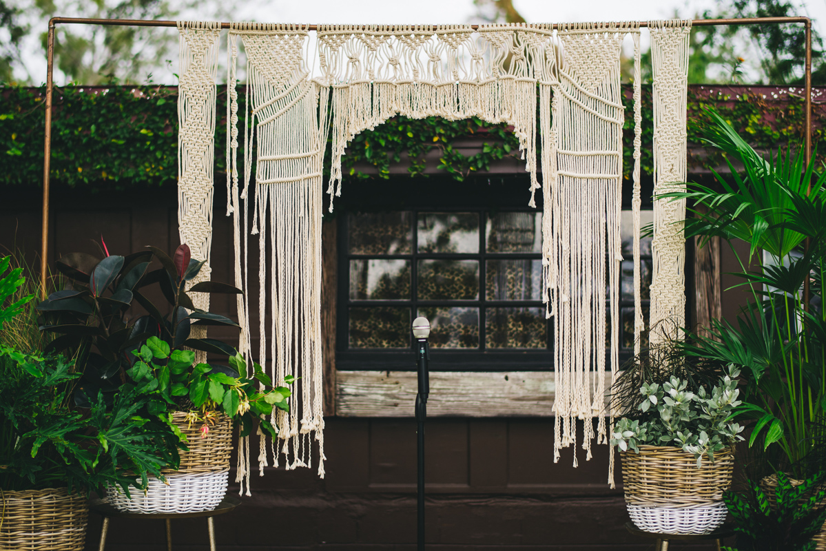 macrame wedding ceremony arch on deck for wedding at The Acre
