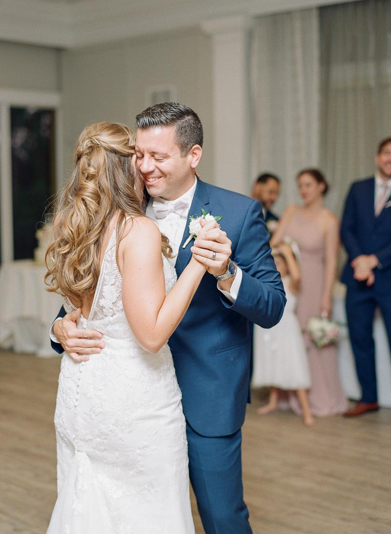 groom smiling while dancing with bride for first dance
