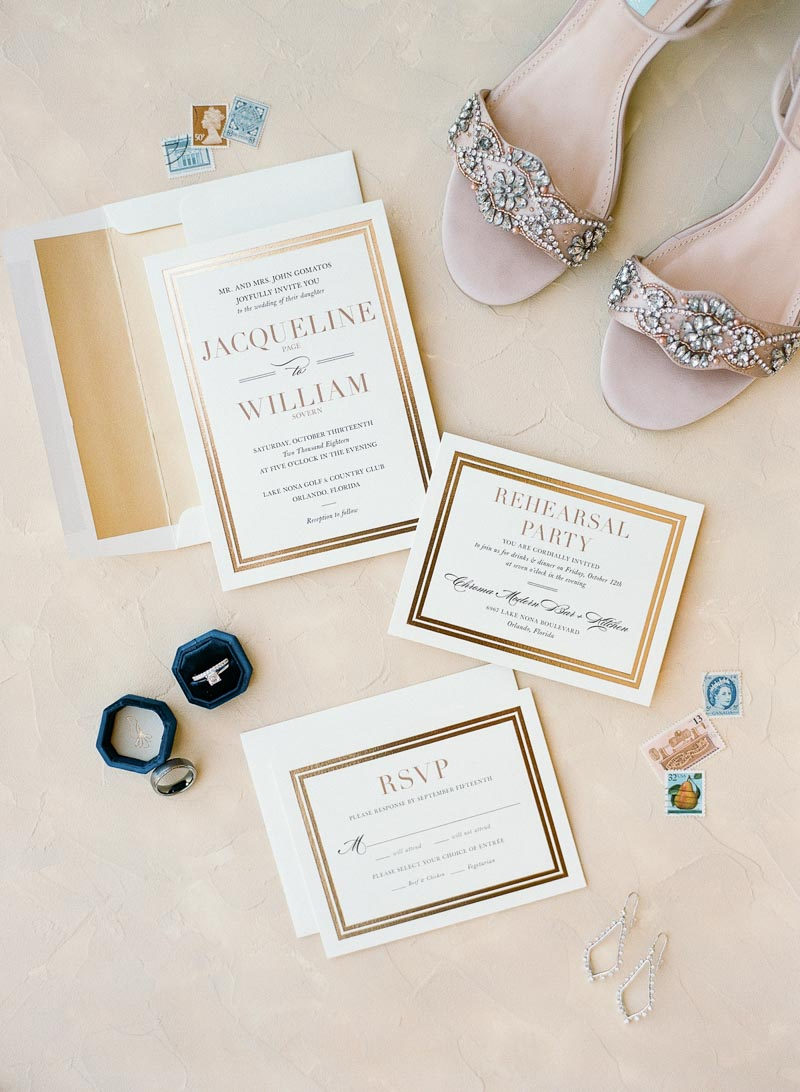 gold trimed wedding invitations on floor next to bride's shoes