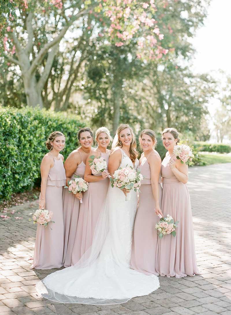 bridesmaids in mauve bridesmaids gowns next to bride