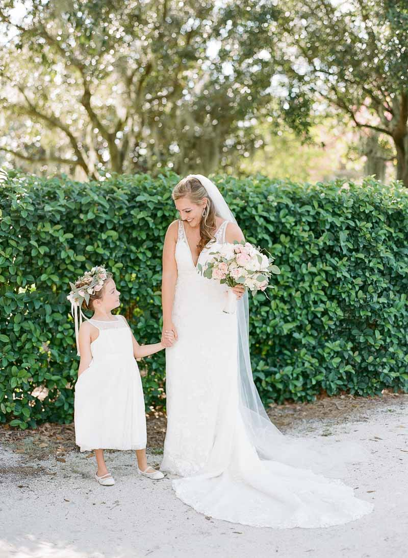 bride smiling and holding flower girls hands