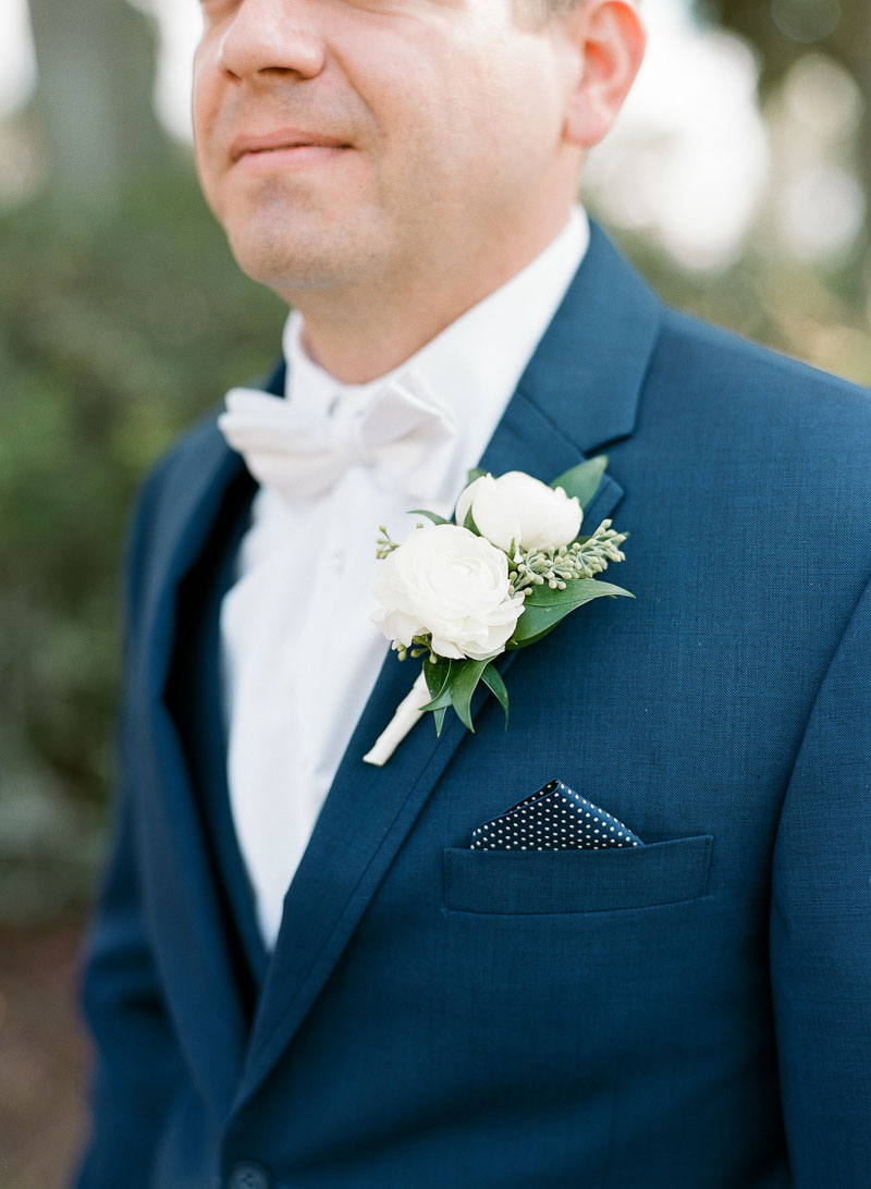 groom in blue suit with white boutonniere