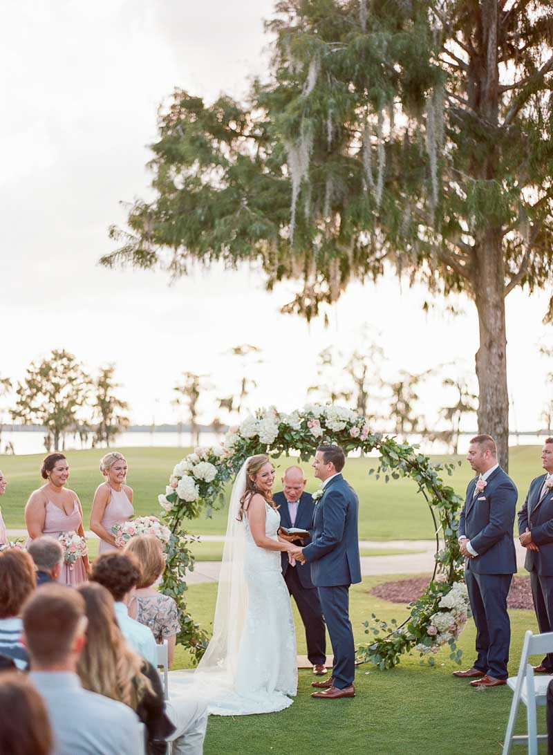 couple getting married outside at the Lake Nona Country Club in front of flower arch