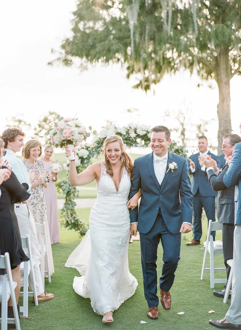 bride holding up bouquet walking down aisle with groom after getting married