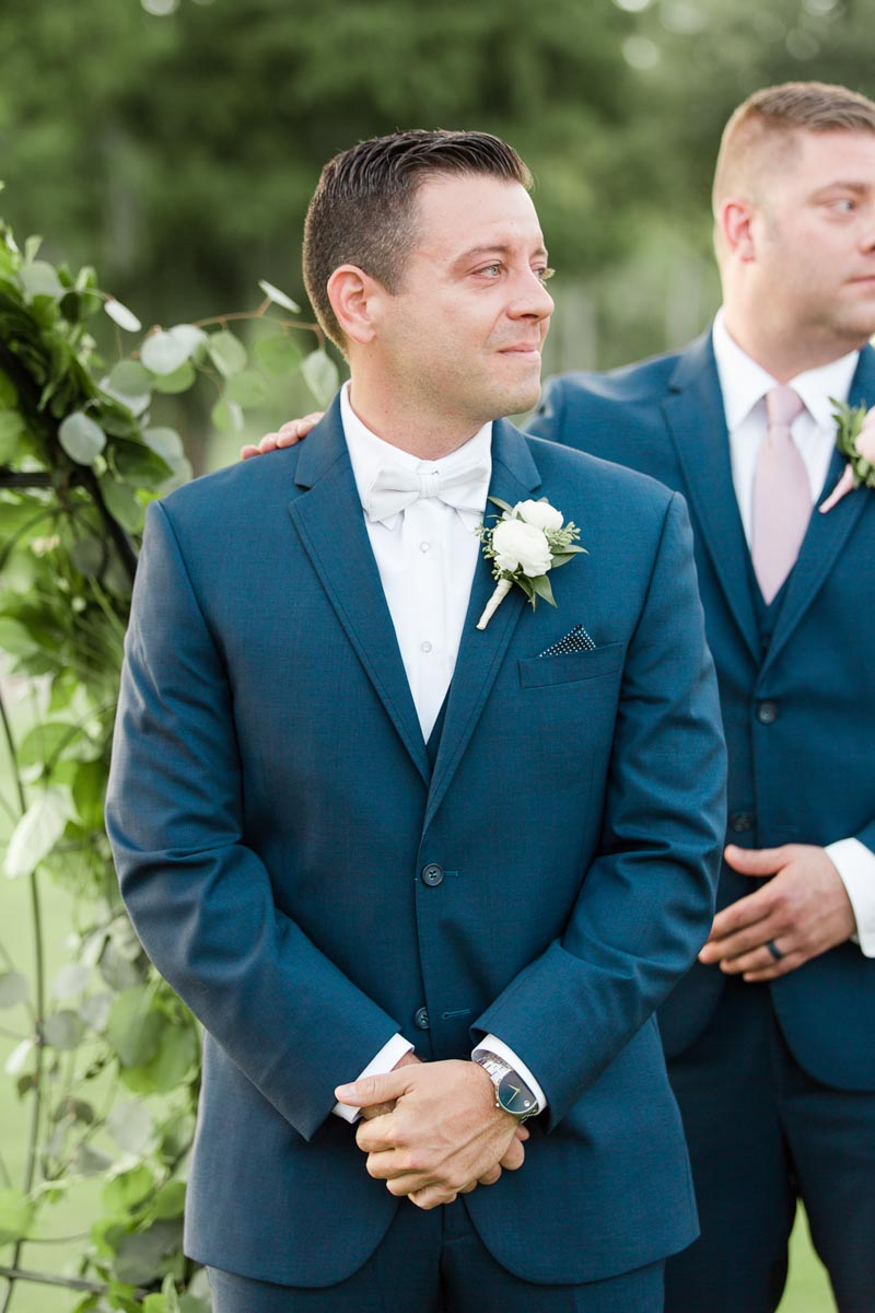 groom in navy suit watching bride walk down the aisle