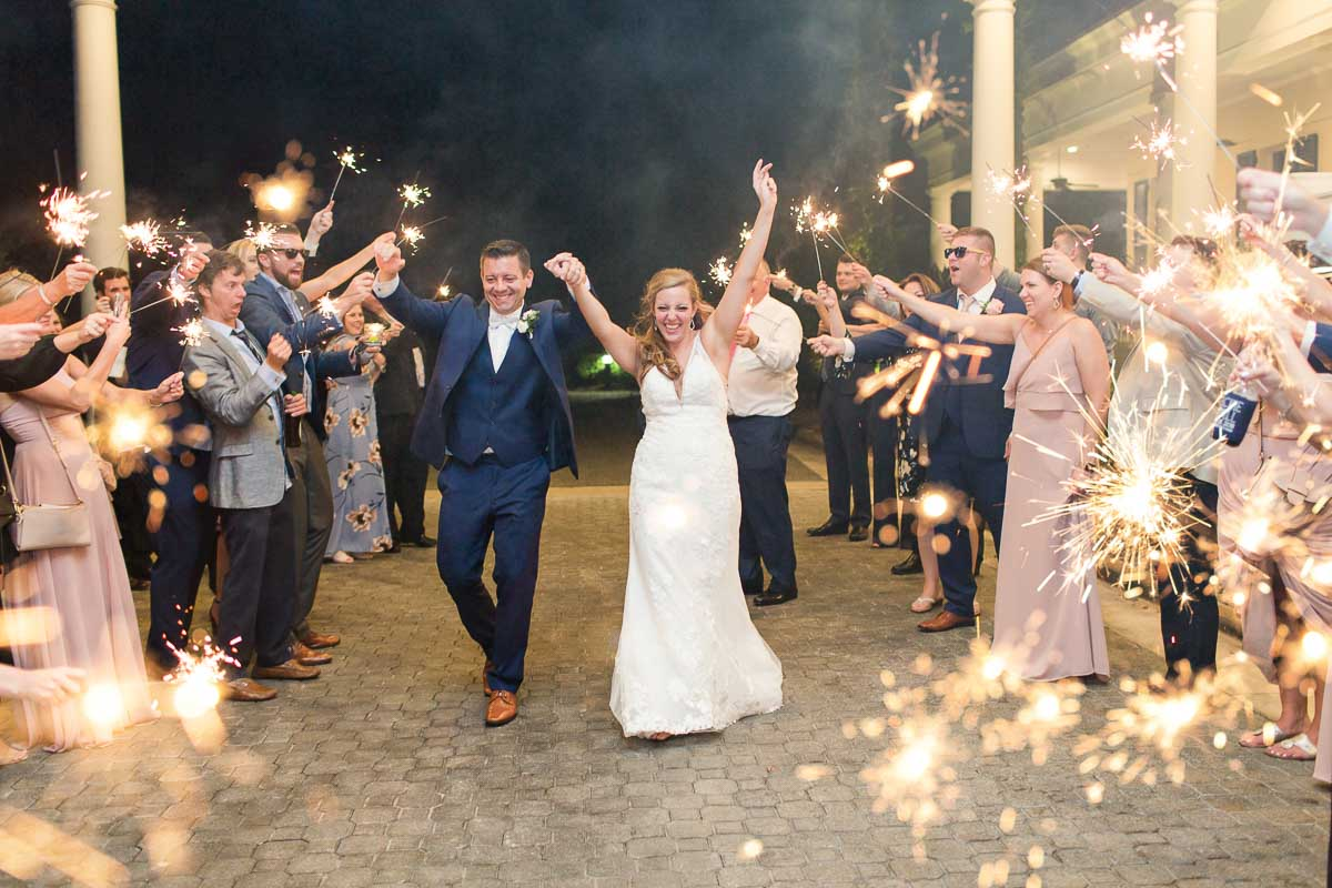 bride and groom raising arms, cheering while walking through sparkler exit
