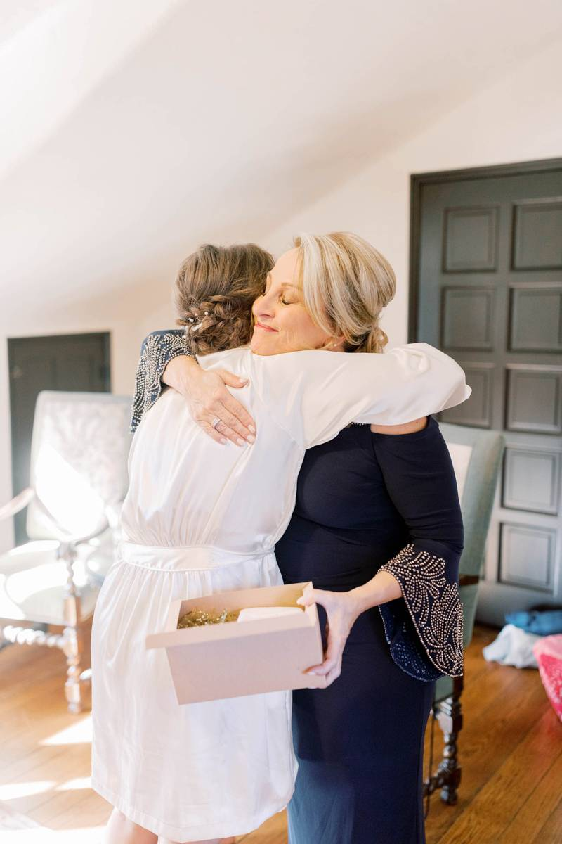 Bride wearing a short white robe hugging her mom after giving her a gift on her wedding day.