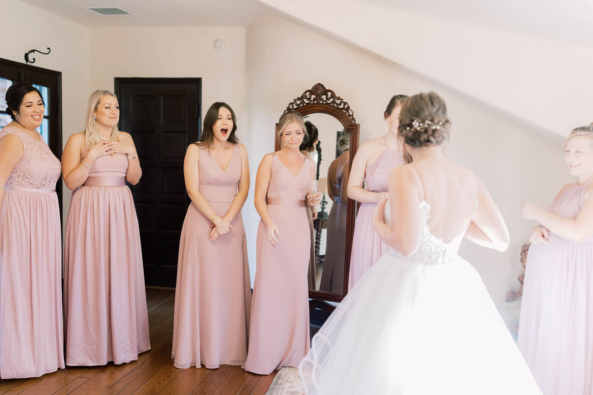 Bridesmaids in blush dresses seeing the bride for the first time. Bridesmaid first look.