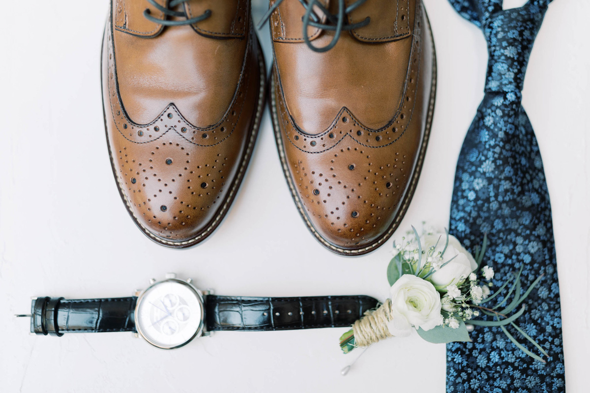 Groom shoes, watch, boutonniere, and tie.