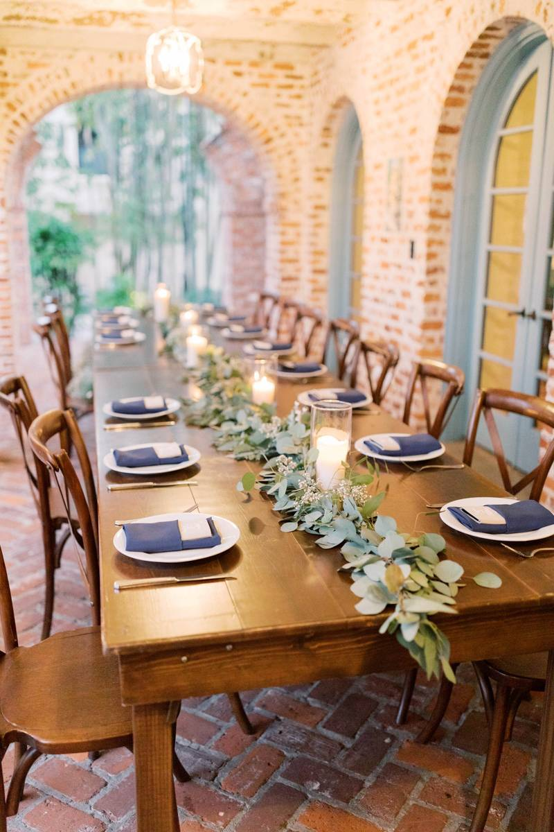 Wooden farmhouse table with eucalyptus leaves and candles.