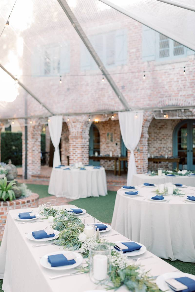 Outdoor Casa Feliz reception with white linens and greenery down the middle of the table. Plates have blue napkins and grey menus.