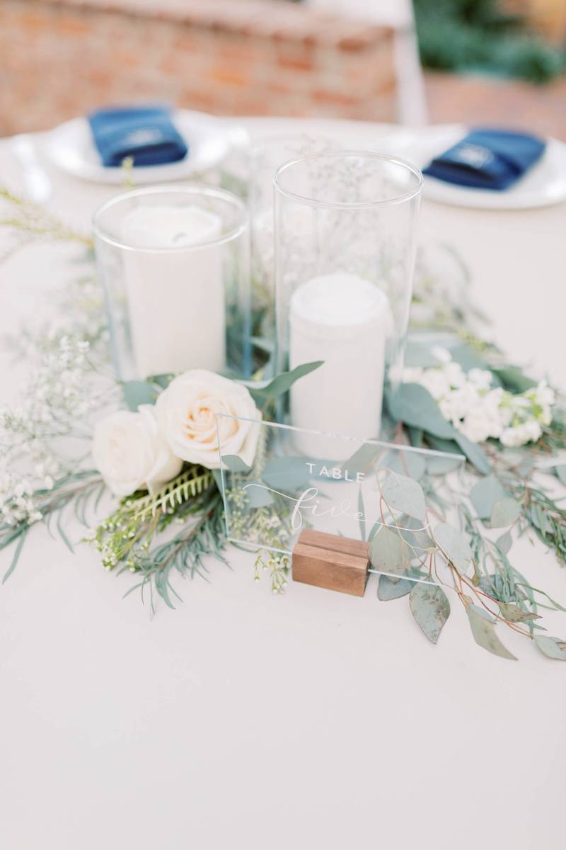 White candles with a table number for wedding decor.