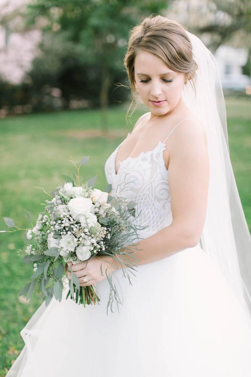 Bride looking over her shoulder holding her bouquet.