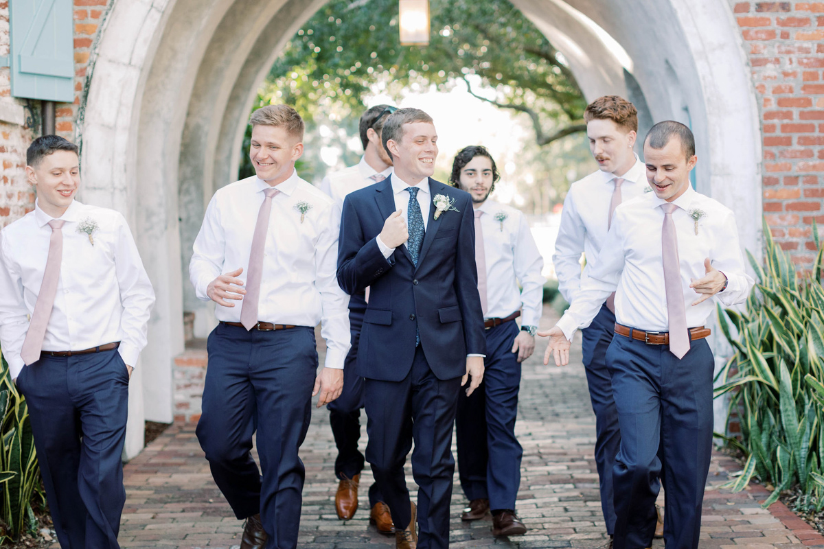 Groom walking with his groomsmen in the archway at Casa Feliz.