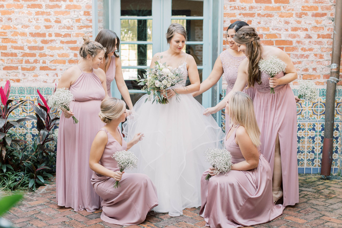 Bride surrounded by her bridesmaids, who are wearing blush.