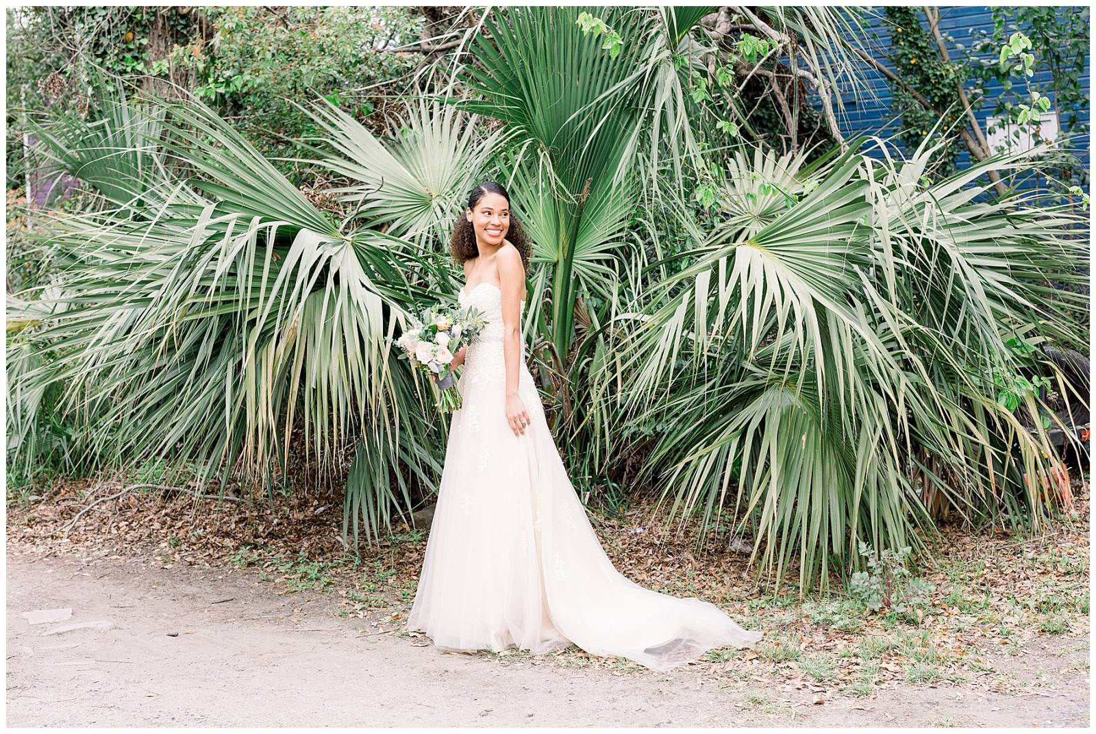 brides holding bouquet standing in front of greenery