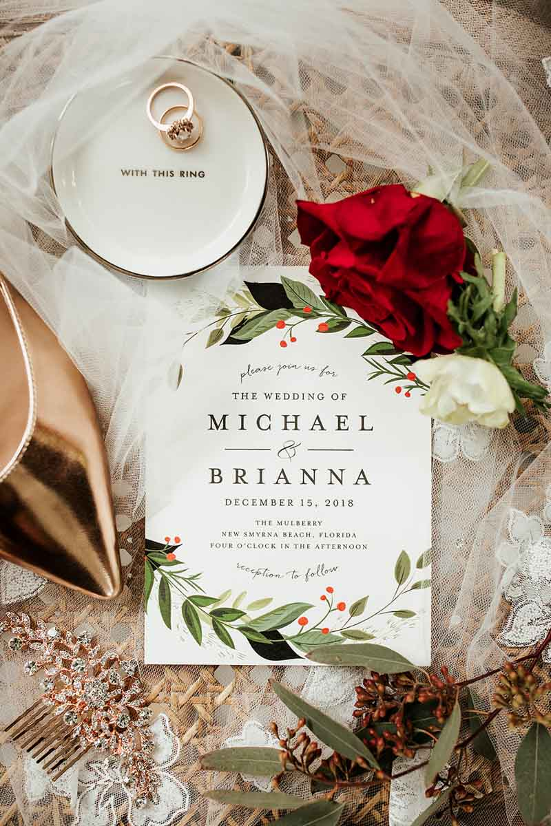 Christmas wedding invitations next to copper bridal shoes