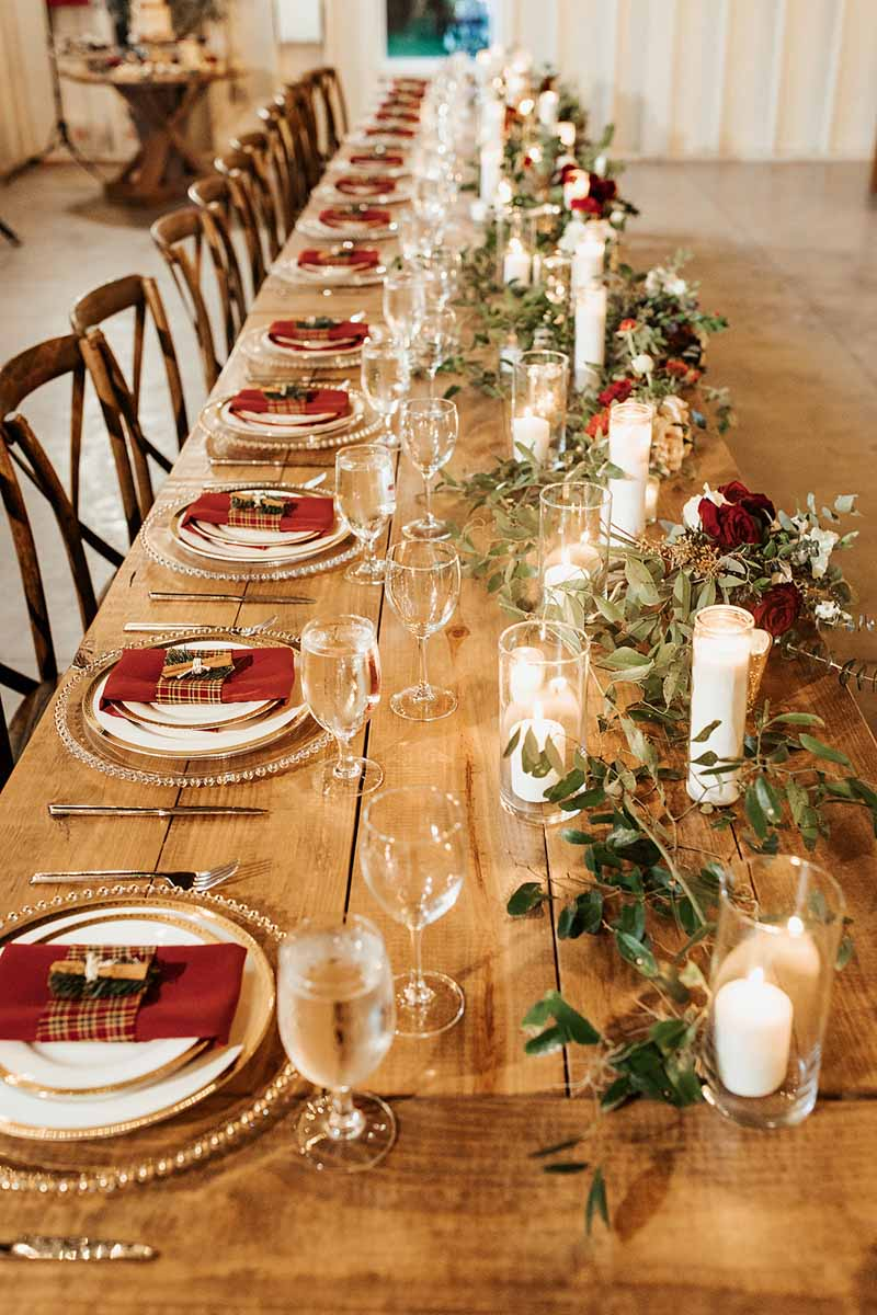 Christmas inspired wedding reception table decor with garland and plaid napkins