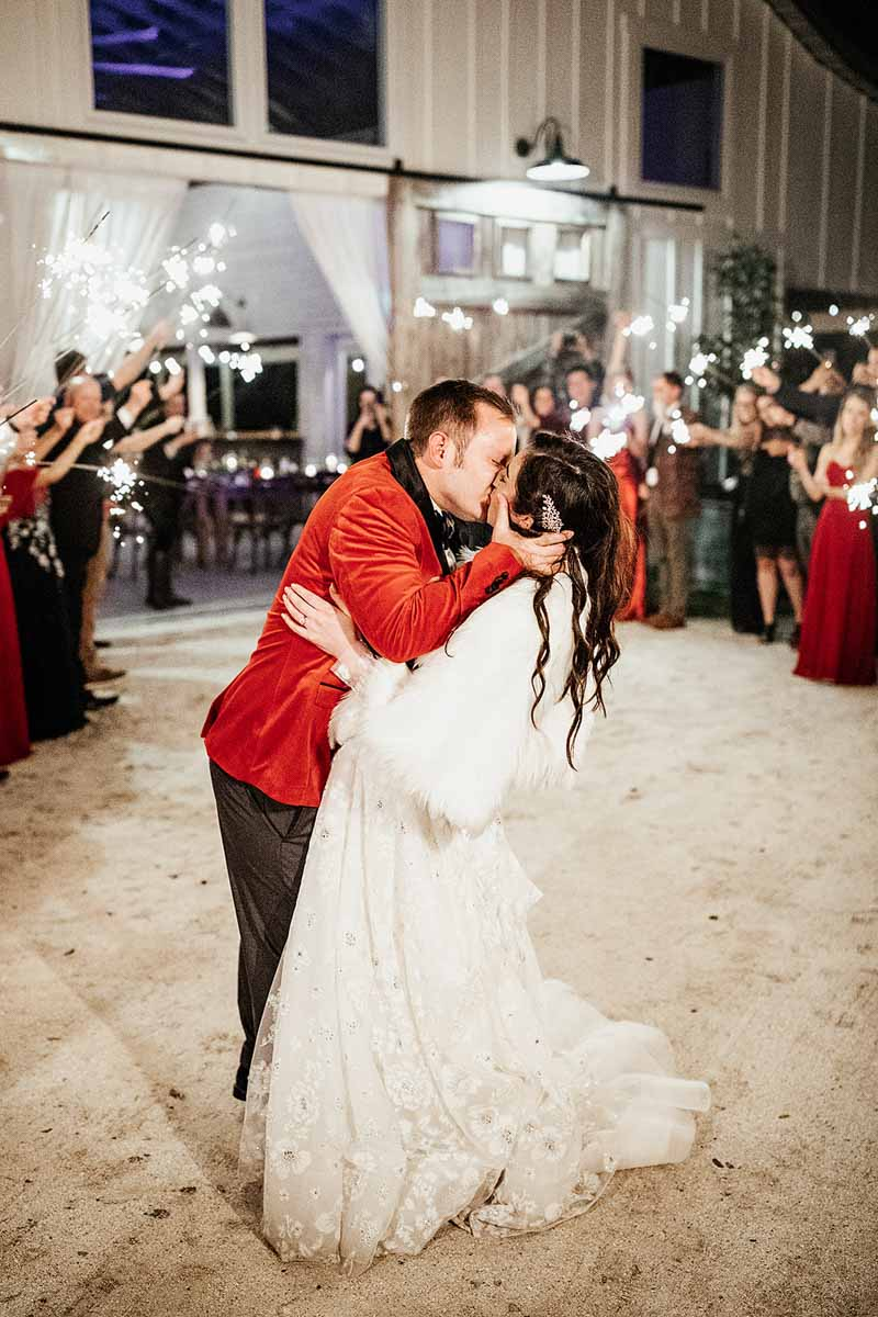 bride in white fur jacket and groom in red suit jacket kissing