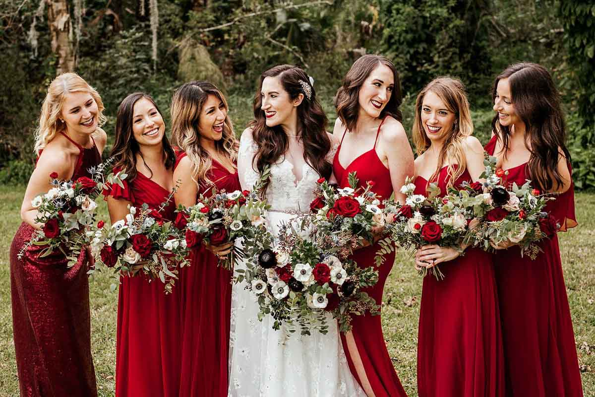 bridesmaids in red dresses hold bouquets with bride