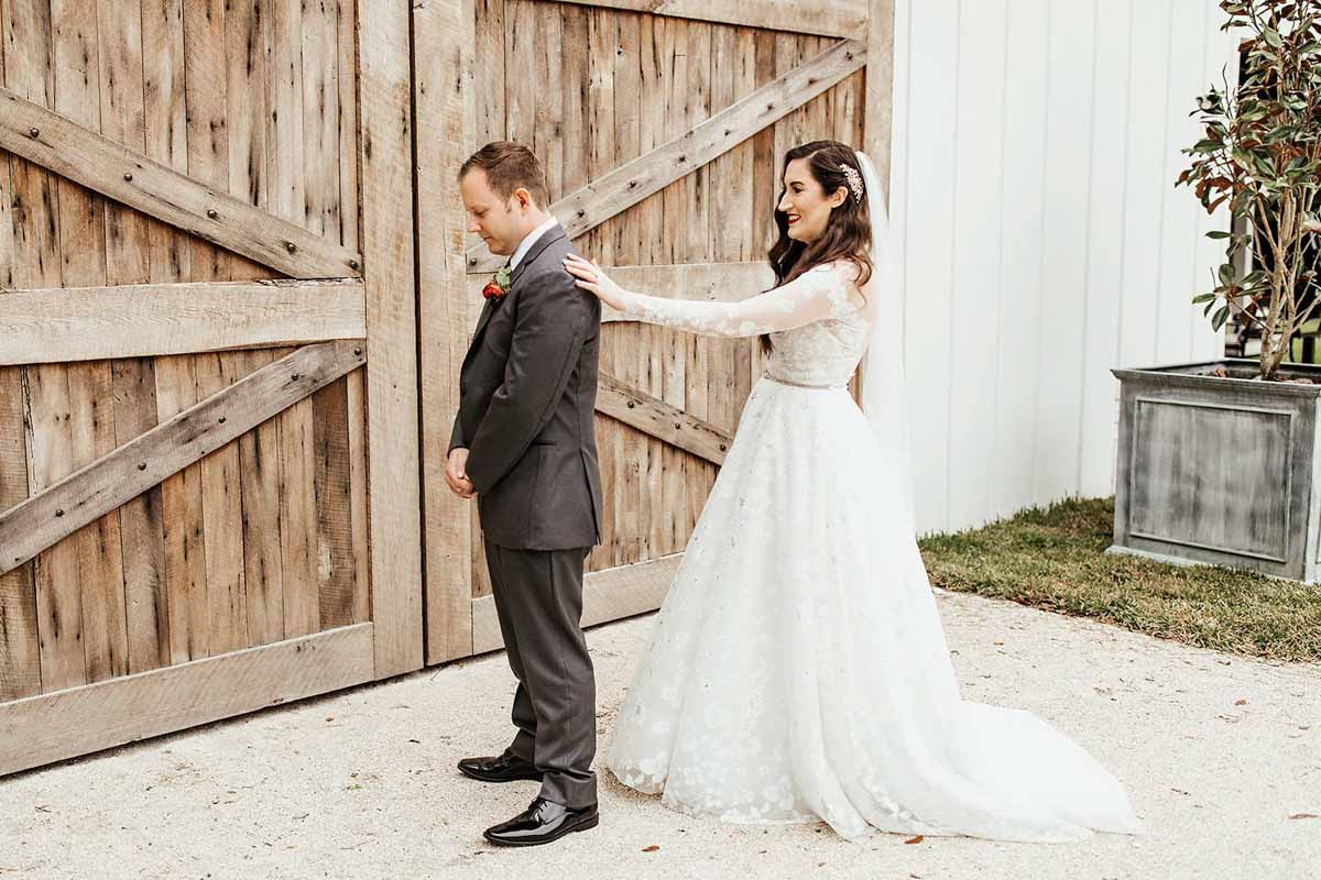 bride tapping grooms shoulder for first look in front of barn
