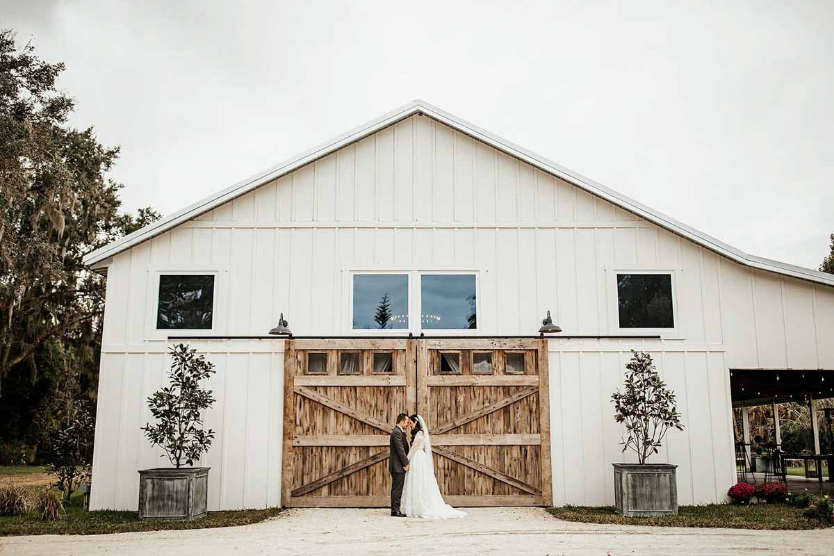 couple standing in front of the reception barn at The Mulberry