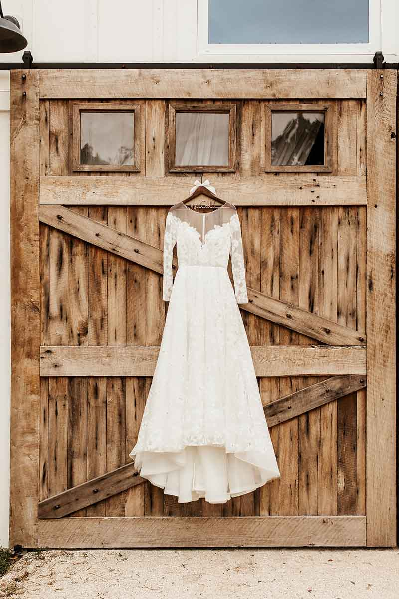 long sleeve bridal gown hanging from the barn at The Mulberry