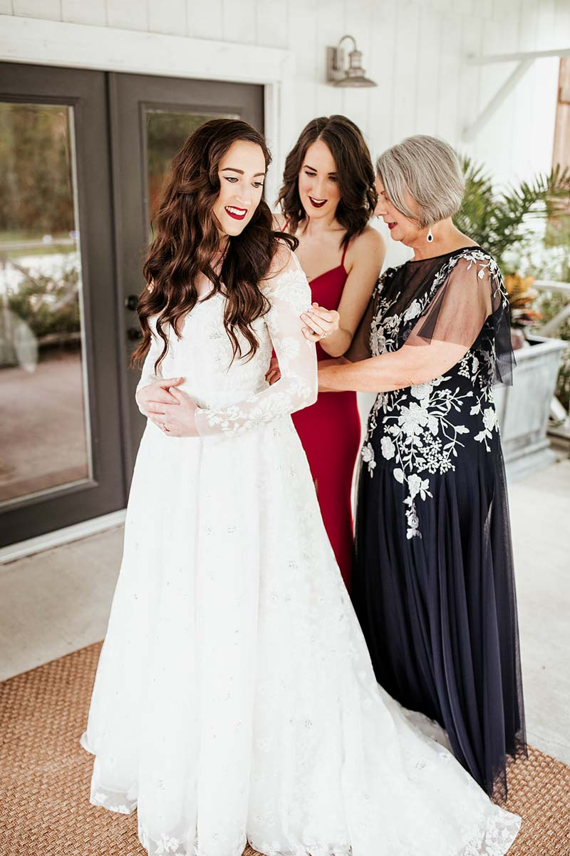 bride's mother and sister helping her in her wedding dress